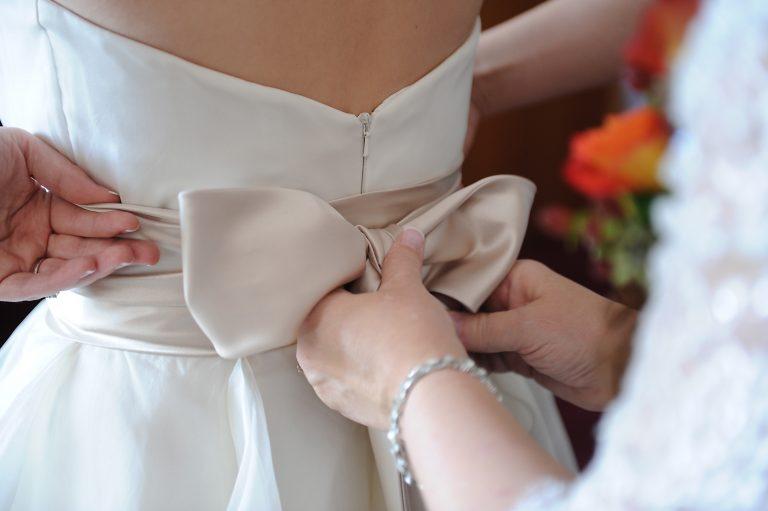Mother straigtening back of wedding dress