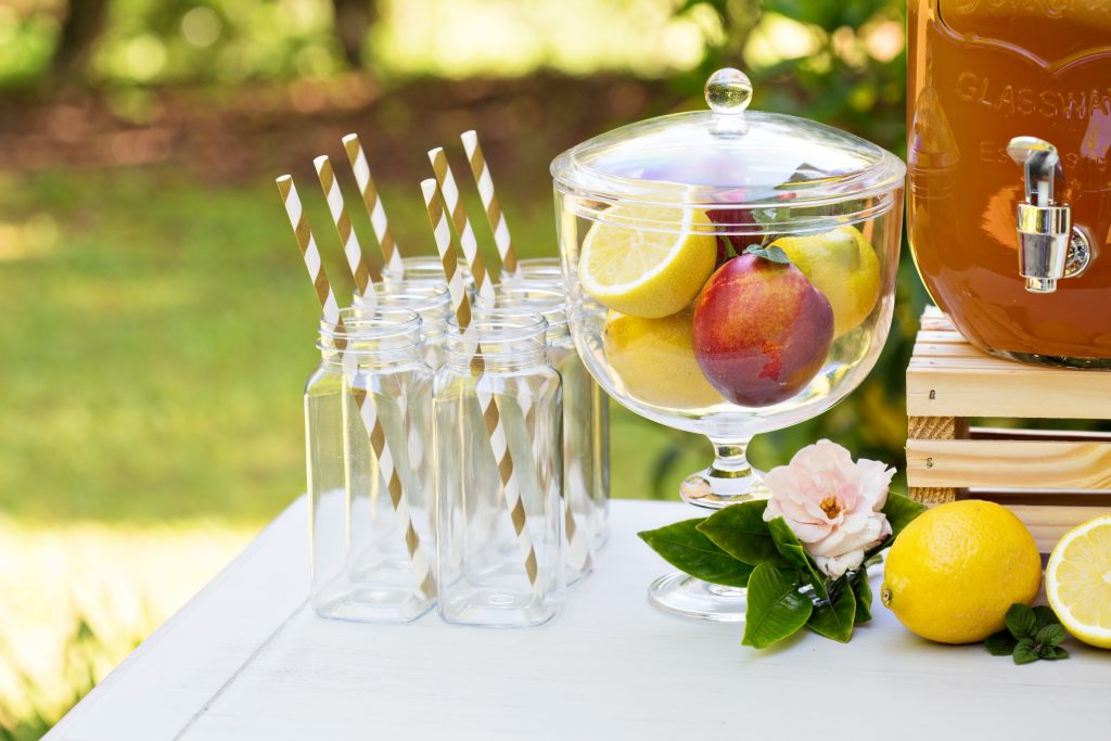 Decorative outdoor party drink station with small bottles and homemade peach lemonade